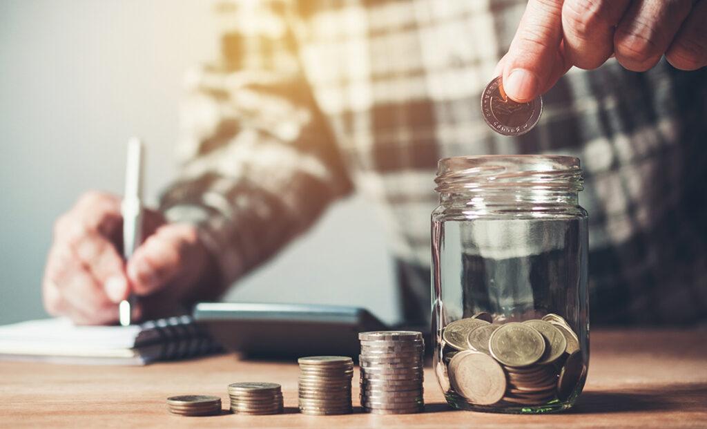 Placing coins in a jar of savings